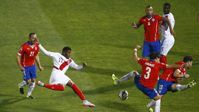 Peru's Ascues  kicks the ball against Chile's Albornoz and Rojas during their Copa America 2015 semi-final soccer match at the National Stadium in Santiago