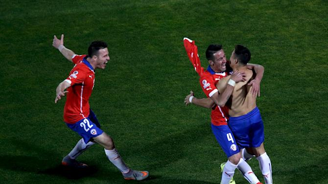 Alexis Sanchez celebrates with teammates Islas and Henriquez after scoring his penalty kick during a shootout against Argentina in the Copa America 2015 final soccer match at the National Stadium in Santiago