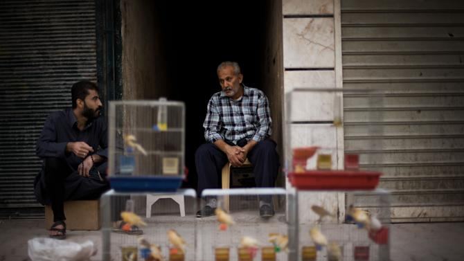 In this Sunday, Oct. 21, 2012 photo, a Syrian street vendor sits in front of his birds in Shaar district in Aleppo, Syria. With death lurking around every corner, the survival instincts of Aleppo's population are being stretched to the limit every day as the battle between Syria's rebels and the regime of President Bashar Assad for the country's largest city stretches through its fourth destructive month. Residents in the rebel-held neighborhoods suffering the war's brunt tell tales of lives filled with fear over the war in their streets, along with an ingenuity and resilience in trying to keep their shattered families going. (AP Photo/ Manu Brabo)