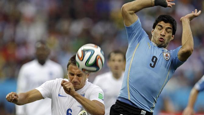 England's Phil Jagielka kicks the ball away from Uruguay's Luis Suarez during the group D World Cup soccer match between Uruguay and England at the Itaquerao Stadium in Sao Paulo, Brazil, Thursday, June 19, 2014
