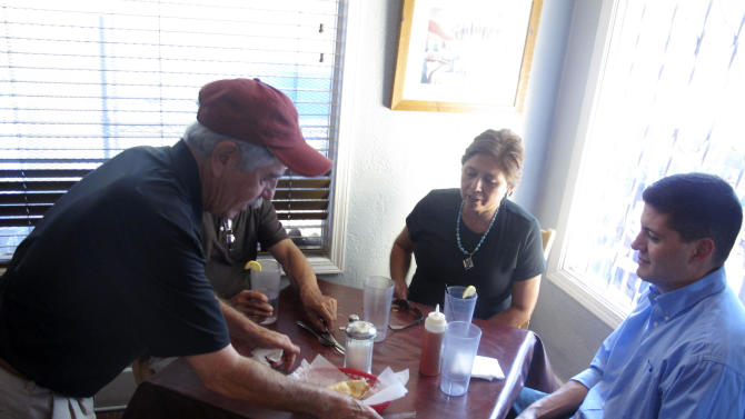 In this Sept 5, 2013 photo, El Patio de Albuquerque owner David Sandoval, left, brings customers sopapillas, a local New Mexican dish. El Patio is a longtime, unpretentious eatery near Albuquerque's University of New Mexico campus. For nearly four decades, multi-generational families, tourists, professors, students _ even celebrities _ have lined up outside this former house for robust but simple fare. (AP Photo/Russell Contreras)