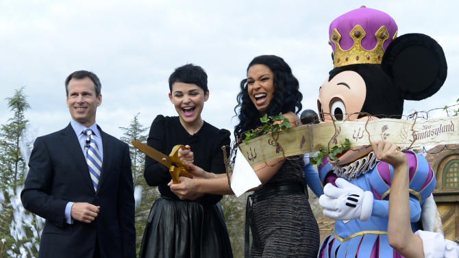 Walt Disney World Parks and Resorts Chairman Tom Staggs, left, and the character Mickey Mouse, right, watch as actress Ginnifer Goodwin, second from left, and singer Jordin Sparks cut the ceremonial ribbon for the New Fantasyland attraction at the Walt Disney World Resort's Magic Kingdom theme park in Lake Buena Vista, Fla., Thursday, Dec. 6, 2012. The new attraction is the largest expansion at the Magic Kingdom.(AP Photo/Phelan M. Ebenhack)