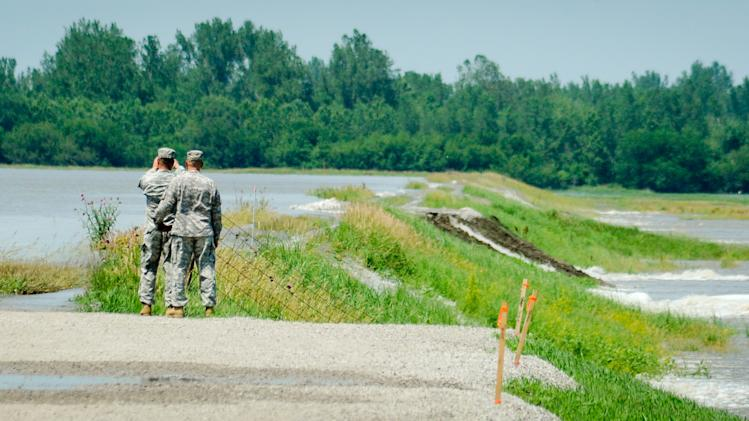 Missouri National Guard soldiers, Staff Sergeant Kevin Ackley, left and Staff Sergeant Allen Godsey look at floodwaters from the Missouri river overtop a levy near Brownville, Neb., Sunday, June, 19, 2011. When the Missouri River reached 42.5 feet, or 899 feet above sea level Sunday morning, the Nebraska Public Power District issued a flooding alert for its nuclear power plant, Cooper Nuclear Station. Cooper, located near Brownville,  is at 903 feet elevation, and NPPD officials said the river would have to climb to 902 feet at Brownville before officials would shut down the plant. (AP Photo/Dave Weaver)