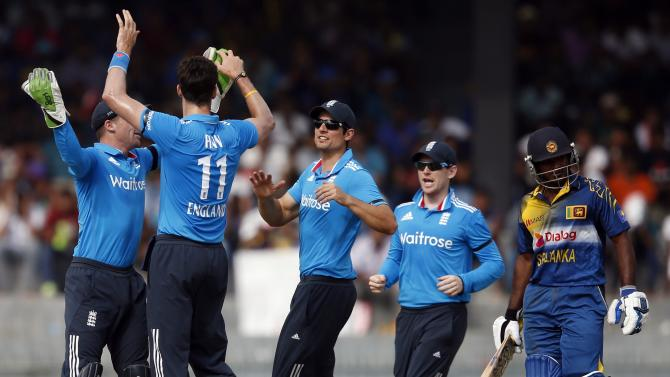 England's captain Cook, Morgan, Buttler and Finn celebrate taking the wicket of Sri Lanka's Perera during their second one-day international (ODI) cricket match in Colombo