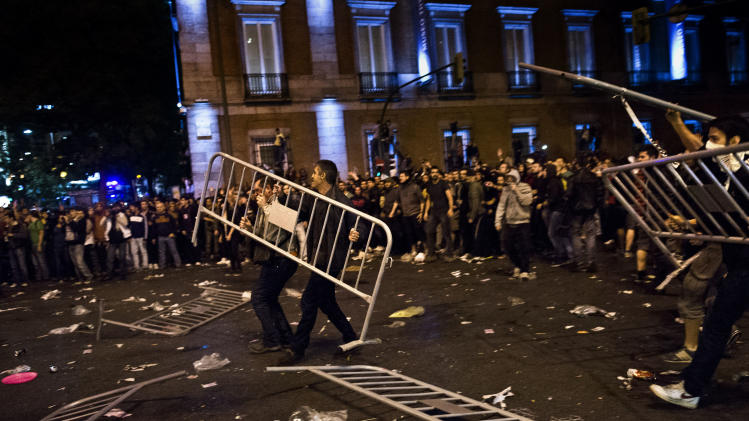 Demonstrators throw fences during riots after a march to the Spanish Parliament against the austerity measures announced by the Spanish government in Madrid, Spain, Tuesday, Sept. 25, 2012. Spain's government was hit hard by the country's financial crisis on multiple fronts Tuesday as protestors enraged with austerity cutbacks and tax hikes clashed with police near Parliament, a separatist-minded region set elections seen as an independence referendum and the nation's high borrowing costs rose again. (AP Photo/Daniel Ochoa De Olza)