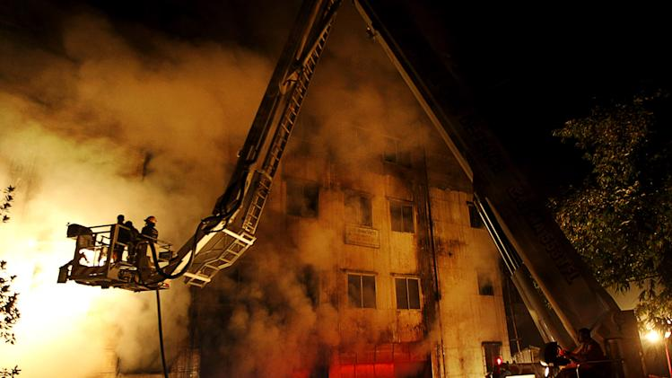 FILE - In this Nov. 24, 2012 file photo, Bangladeshi firefighters battle a fire at a garment factory in the Savar neighborhood in Dhaka, Bangladesh. A Bangladesh government committee investigating the garment factory fire that killed 112 people last month said in its findings Monday, Dec. 17, 20112 that the blaze was sabotage, probably by someone who worked there. But the panel said that no matter who set the fire, the owner of the factory also should be punished for the deaths because he neglected worker safety. (AP Photo/Hasan Raza, File)