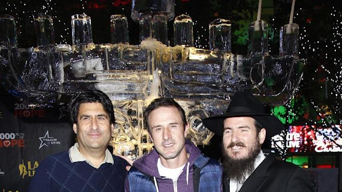 AEG's V.P. of Communications Michael Roth, David Arquette and Chabad's Rabbi Cunin pose for photo during AEG's Season of Giving celebrates Chanukah with David Arquette and Chabad's Rabbi Cunin on Sunday, December, 9, 2012 in Los Angeles. (Photo by Joe Kohen/Invision for AEG/ AP Images)