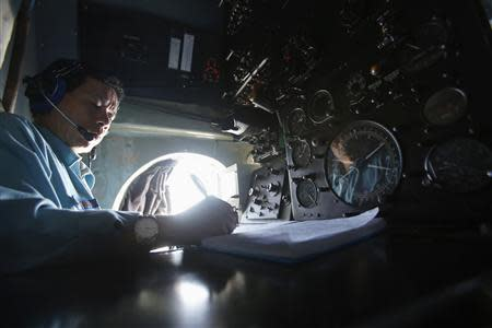 Senior Lieutenant Phung Truong Son takes notes while working within the cockpit of a Vietnam Air Force AN-26 aircraft during a mission to find the missing Malaysia Airlines flight MH370, off Con Dao island