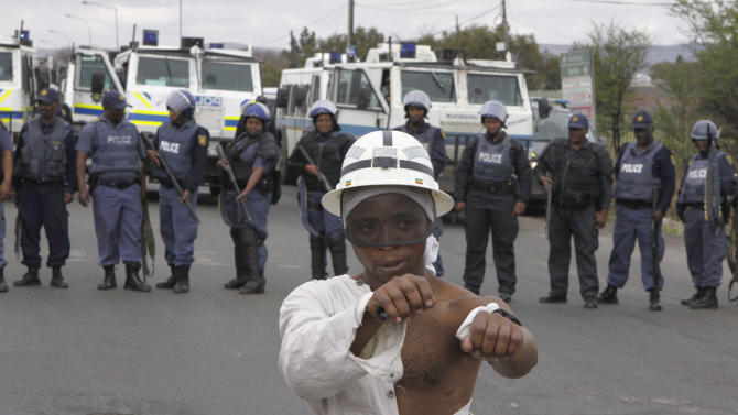 A striking platinum miner takes part in a march to the Rustenburg, South Africa, police station, Sunday, Sept. 16, 2012 to protest the heavy handed way the police are cracking down on strikers who have been off work since early last month. The march was declared illegal by the police, who prevented the protesters from entering the town, and the strikers dispersed peacefully. (AP Photo/Denis Farrell)