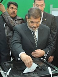 <p>Egyptian President Mohamed Morsi casts his vote at a polling station near the presidential palace in Cairo on December 15, 2012. Much of the judiciary is also stepping up its challenge to Morsi's authority and the proposed charter, which is being put to voters in a split referendum held last Saturday and the coming Saturday.</p>