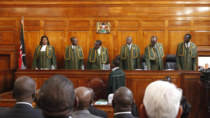 Six Supreme Court judges, led by Chief Justice Willy Mutunga, third left, arrive at court to hear the petition by Kenya's Prime Minister Raila Odinga filed against president-elect Uhuru Kenyatta at the Supreme Courts in Nairobi, Kenya, Monday, March 25, 2013.  The court ordered the election commission to recount votes in 22 of the country's 291 constituencies to see if any of the tallies exceed the number of registered voters, after Uhuru Kenyatta was named the winner of the March 4 Presidential election with 50.07 per cent of the vote.(AP Photo/Sayyid Azim)