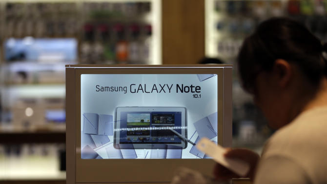 A woman walks by a billboard of Samsung Electronics's Galaxy Note 10.1 at a showroom of its headquarters in Seoul, South Korea, Friday, Oct. 5, 2012. Samsung Electronics Co. tipped all-time high quarterly operating profit, likely driven by strong sales of high-end smartphones that offset weak semiconductor orders. (AP Photo/Lee Jin-man)