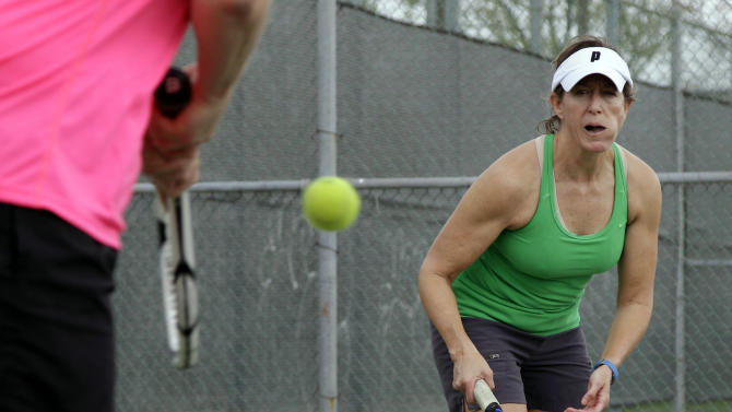 Laura Ferlic-Stark, right, 50, of Plano, Texas, keeps her eye on the ball as her practice partner Marilyn Leher, left, returns a volley during an instructional class at High Point Tennis Center Wednesday, March 14, 2012, in Plano, Texas. Ferlic-Stark said that cycling and soccer are other fitness activities she participates in to keep healthy. (AP Photo/Tony Gutierrez)