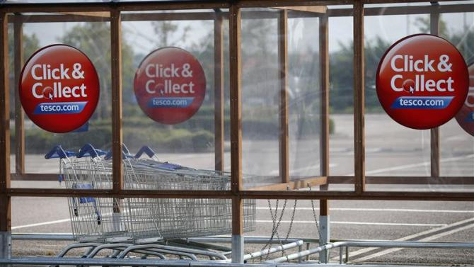 A click and collect adverts are seen on a shopping trolley stand at Tesco store in Leicester