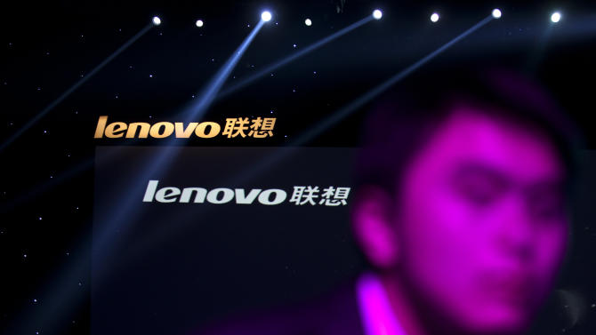 In this Aug. 6, 2012 photo, a Lenovo employee, front, walks near the company logos during a Lenovo promotional event in Beijing, China. Beijing-based Lenovo, the world's second-largest personal computer maker, said Thursday, Aug. 16, 2012 it earned $144 million in the three months ending June 30. The profit growth rate was down from the previous quarter's 59 percent increase. (AP Photo/Alexander F. Yuan)