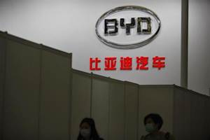 Women walk in front of the logo of Chinese car manufacturer BYD Auto stage before the opening of the 15th Shanghai International Automobile Industry Exhibition
