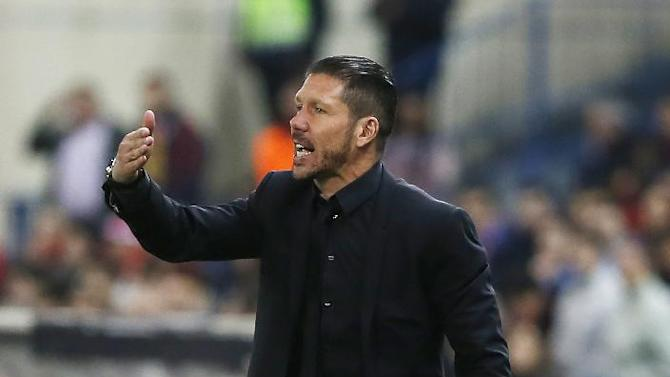 Atletico's coach Diego Simeone from Argentina, talks to his players during a Spanish La Liga soccer match between Atletico Madrid and Espanyol at the Vicente Calderon stadium in Madrid, Spain, Saturday, March 15, 2014