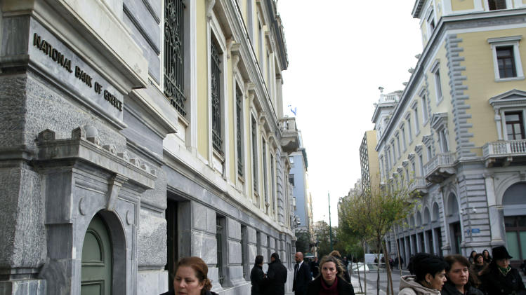 Athenians walk past a central Athens branch of  National Bank of Greece, the country's largest lender, Tuesday, Dec. 11, 2012. Greece was expected to announce later Tuesday the results of a bond buyback hoped to cut some 20 billion euros off the country's 340 billion euro debt load. Domestic lenders will contribute strongly in the European-funded buyback, which if successful will open the way for disbursement of a delayed international rescue loan payment. (AP Photo/Petros Giannakouris)