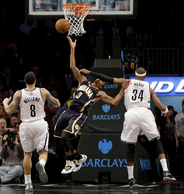 Brooklyn Nets' Paul Pierce, right, commits a flagrant foul against Indiana Pacers' George Hill, center, while Deron Williams watches during the second half of an NBA basketball game Monday, De