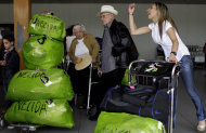 "Cubans who live in the U.S. arrive with packages that read ""Nelida"" to the Jose Marti International Airport as they arrive to Havana, Cuba, Monday, Sept. 3, 2012. A steep hike in customs duties has taken effect Monday in Cuba, catching some air travelers unaware. Nelida Diaz, center left, says she was shocked when officials charged her $588 at customs. The woman at right is speaking to a person who came to get her at the airport. (AP Photo/Franklin Reyes)"