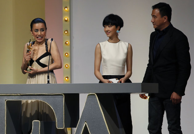 "Japanese actress Watanabe Makiko reacts after she receives the Best Supporting Actress award for the film "" Capturing Dad ""at the Asian Film Awards in Hong Kong Monday, March 18, 2013. At right is Chinese actor Hu Jun and Taiwanese actress Gwel Lun-mei, center,. (AP Photo/Vincent Yu)"