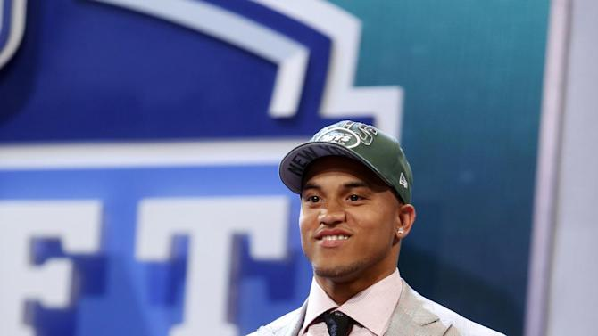 Dee Milliner, from Alabama, holds up a team jersey after being selected ninth overall by the New York Jets in the first round of the NFL football draft, Thursday, April 25, 2013, at Radio City Music Hall in New York. (AP Photo/Jason DeCrow)