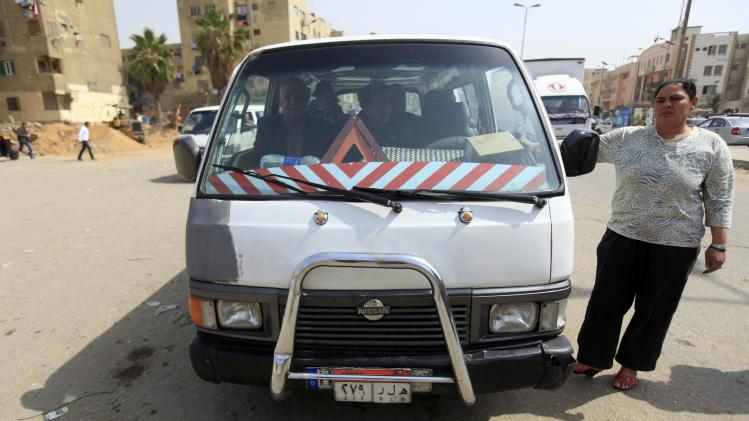 "Nahed, or ""Um Rania"", 52, stands next to her minibus as she waits for passengers at a station in Cairo"
