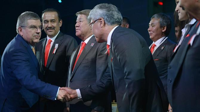 International Olympic Committee (IOC) President Thomas Bach, left, shakes hands with a delegation member from Kazakh city of Almaty as Kazakhstan's Prime Minister Karim Massimov, second left, looks on after Beijing was selected to host the 2022 Olympic Winter Games at IOC meeting during the 128th IOC session in Kuala Lumpur, Malaysia, Friday, July 31, 2015. The Chinese capital, which hosted the 2008 Summer Olympics, came in to the vote against the city from Kazakhstan as the strong favorite, despite its lack of natural snow. (Mohd Rasfan/Pool Photo via AP)