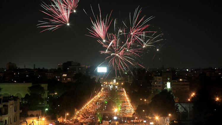 """Fireworks light the sky as opponents of Egypt's Islamist President Mohammed Morsi protest outside the presidential palace in Cairo, Egypt, Monday, July 1, 2013. Egypt's powerful military warned on Monday it will intervene if the Islamist president doesn't """"meet the people's demands,"""" giving him and his opponents two days to reach an agreement in what it called a last chance. Hundreds of thousands of protesters massed for a second day calling on Mohammed Morsi to step down. (AP Photo/Khalil Hamra)"""