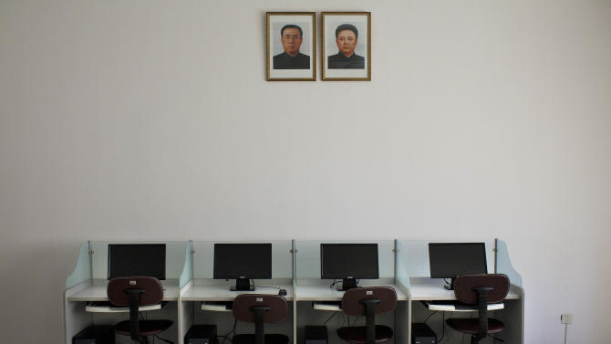 FILE - In this Oct. 5, 2011 file photo, portraits of North Korea's late leaders Kim Il Sung, left, and Kim Jong Il hang on a wall over a bank of computers at Pyongyang University of Science and Technology. North Korea is literally off the charts regarding Internet freedoms. There essentially aren't any. But the country is increasingly online. Though it deliberately and meticulously keeps its people isolated and in the dark about the outside world, it knows it must enter the information age to survive in the global economy. (AP Photo/David Guttenfelder, File)
