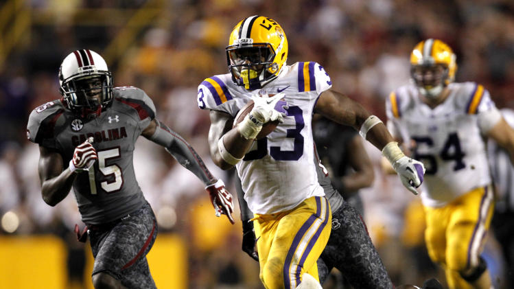 LSU running back Jeremy Hill (33) carries for a 50-yard touchdown as South Carolina cornerback Jimmy Legree (15) pursues during the second half of an NCAA college football game in Baton Rouge, La., Saturday, Oct. 13, 2012. LSU won 23-21. (AP Photo/Gerald Herbert)