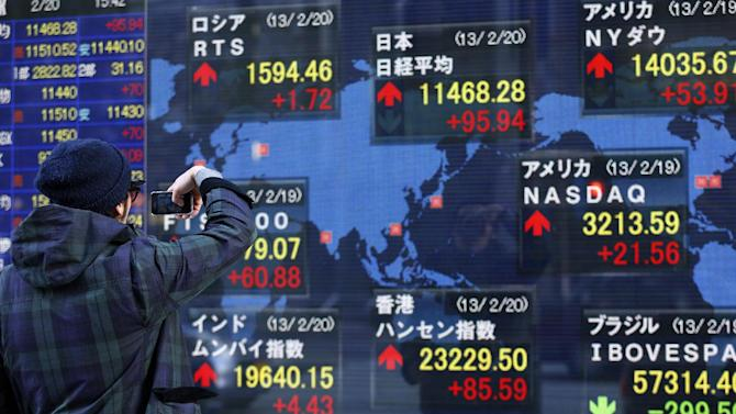 FILE - In this Wednesday, Feb. 20, 2013, file photo, a man takes a photograph of the electronic stock board of a securities firm in Tokyo. U.S. stocks are not alone in racing ahead this year. Many markets in Europe and Asia are trading at multi-year highs, too, in part because of Wall Street's rally. (AP Photo/Shizuo Kambayashi, File)