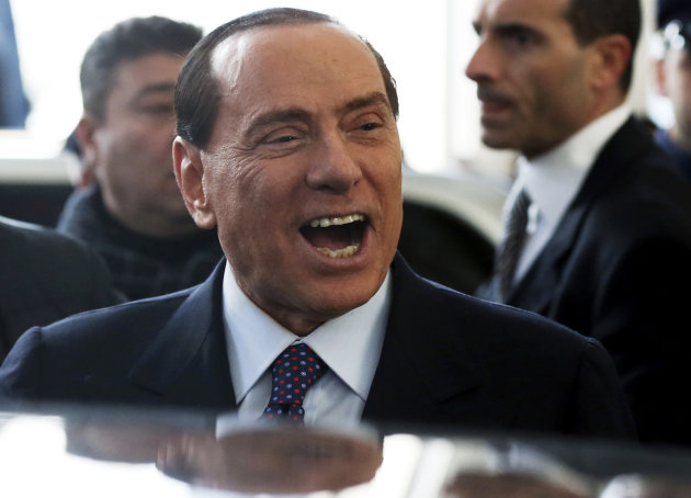 "FILE - In this Dec. 29, 2012 file photo Silvio Berlusconi smiles as he arrives at Milan's central train station. Former Premier Silvio Berlusconi announced a deal Monday, Jan. 7, 2013 with the Northern League, his fractious coalition partner in three governments, to jointly run in Italy's election next month. The move could give fresh impetus to the center-right and extend the Berlusconi era. While leaving open the question of whether he will run himself, Berlusconi underlined his ambitions for the deal reached overnight at his villa near Milan by saying: ""Habemus Papum,"", the Latin phrase for ""We have a pope."" (AP Photo/Luca Bruno)"