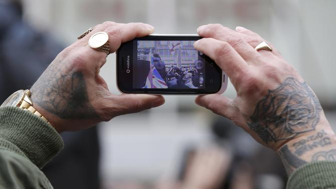A man uses a mobile phone to photograph a demonstration by supporters of the Pegida movement in Newcastle, northern England