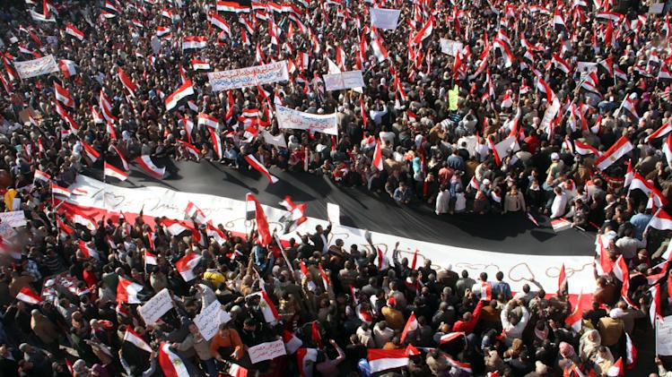 Egyptian Egyptian supporters of the ruling supreme council of the armed forces, SCAF, surround a giant national flag during their rally to support the council at Abbasiya Square in Cairo, Egypt Friday, Dec. 23, 2011. (AP Photo)