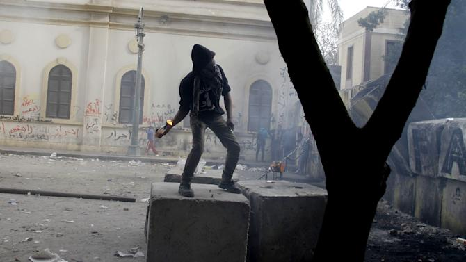 A Protester moments before throwing a Molotov cocktail toward Egyptian riot police, unseen, near Tahrir Square in Cairo, Egypt, Thursday, Jan. 24, 2013. Egypt's black-clad riot police fired tear gas in fierce dawn clashes with dozens of protesters on Thursday when they tried to tear down a cement wall built to prevent demonstrators from reaching parliament and the Cabinet building. The violence which was soothed hours later in central Cairo comes on eve of the second anniversary of Egypt's Jan. 25 uprising, which toppled longtime authoritarian president Hosni Mubarak in 2011. (AP Photo/Mostafa El Shemy)