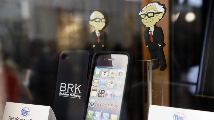 A Berkshire Hathaway cell phone case and a USB port featuring the cartoon likeness of Warren Buffett, right, and Charlie Munger, left, are offered for sale at a reception held for shareholders at the Borsheims jewelry store in Omaha, Neb., Friday, May 3, 2013. More than 30,000 people are expected to attend Saturday's Berkshire Hathaway shareholder meeting to hear Warren Buffett and Charlie Munger answer questions for more than six hours. No other annual meeting can rival Berkshire's, which is known for its size, the straight talk Buffett and Munger offer and the sales records shareholders set while buying Berkshire products. (AP Photo/Nati Harnik)