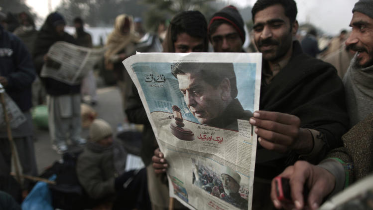 Supporters of Pakistani Sunni Muslim cleric Tahir-ul-Qadri, read a local newspaper featuring an image of Pakistan's Prime Minister Raja Pervaiz Ashraf, as they camp near parliament, during an anti-government rally in Islamabad, Pakistan, Wednesday, Jan. 16, 2013. Pakistan's leaders received a powerful one-two punch Tuesday as the Supreme Court ordered the arrest of the prime minister in a corruption case and the firebrand cleric led thousands of protesters in another day of anti-government demonstrations in the capital. (AP Photo/Muhammed Muheisen)