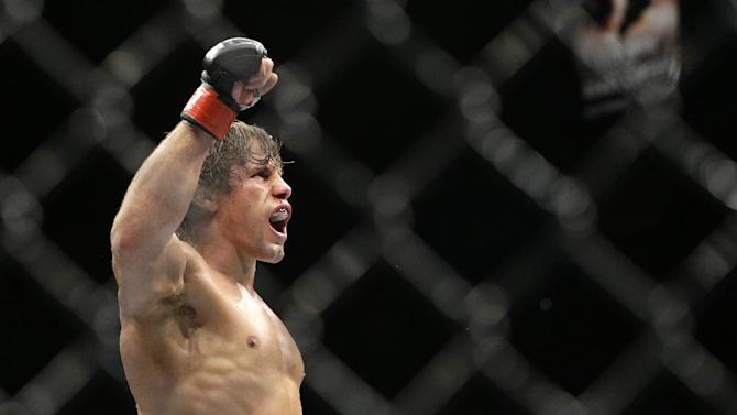 Urijah Faber celebrates after defeating Alex Caceres in their bantamweight mixed martial arts bout at UFC 175 on Saturday, July 5, 2014, in Las Vegas