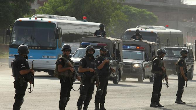 Pakistani security personnel stand alert as Zimbabwe and Pakistani teams arrive at the Gaddafi stadium for a practice session in Lahore, Pakistan, Wednesday, May 17, 2015. Zimbabwe is the first test playing nation to visit Pakistan in more than six years since gunmen attacked on a bus for the Sri Lanka team in Lahore in 2009. (AP Photo/K.M. Chaudary)
