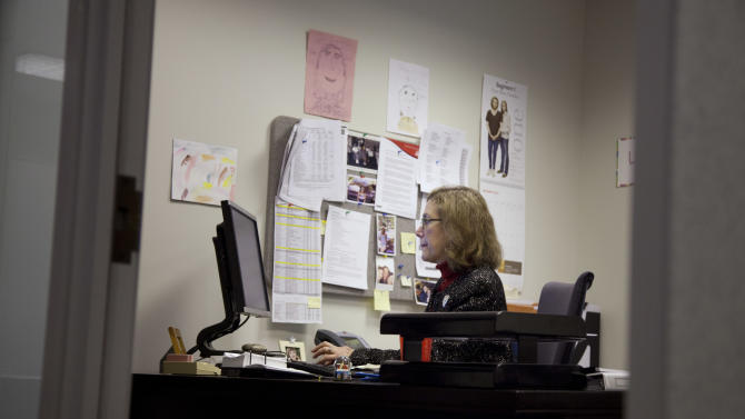 Lynn Feinberg, a caregiver expert at AARP, works in her office on Thursday, Jan. 26, 2012 in Washington. As lifespans lengthen and the number of seniors rapidly grows, more Americans find themselves struggling to care for an ailing loved one from hundreds or thousands of miles away. Feinberg said the number of long-distance caregivers is likely to grow, particularly as a sagging economy has people taking whatever job they can get, wherever it is.    (AP Photo/Evan Vucci)