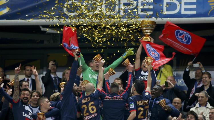 Paris St Germain's players celebrate with their trophy after defeating Olympique Lyon in the French League Cup final soccer match at the Stade de France stadium in Saint-Denis