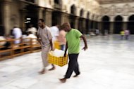 Men carry food and water in Cairo on Saturday for the Iftar meal to break the fast on the first day of Ramadan. Al-Azhar, Sunni Islam's main seat of learning based in Cairo, has issued a fatwa against a new TV series saying that portrayals of Prophet Mohammed and his companions are forbidden