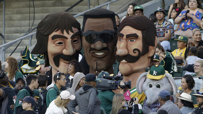 Contestants dressed as former Oakland Athletics players Dennis Eckersley, left, Rickey Henderson, center, and Rollie Fingers stand with fans after racing during the seventh inning of a baseball game between the Athletics and the Seattle Mariners in Oakland, Calif., Friday, July 3, 2015. (AP Photo/Jeff Chiu)