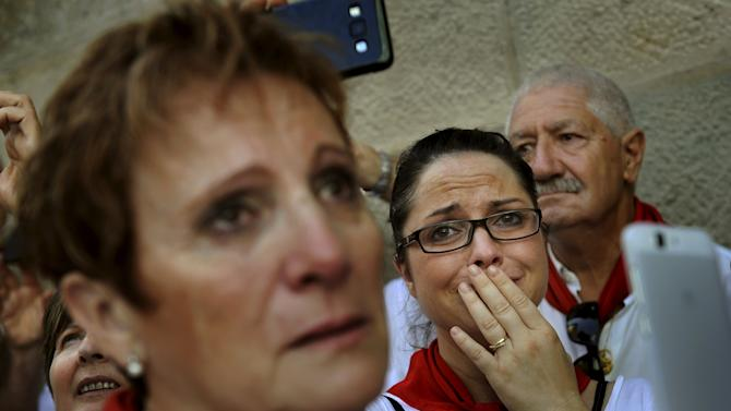 A woman cries during a procession in honour of San Fermin on the saint's day at the San Fermin festival in Pamplona