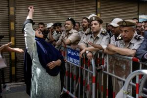 An Egyptian woman mourns as policemen stand guard after …
