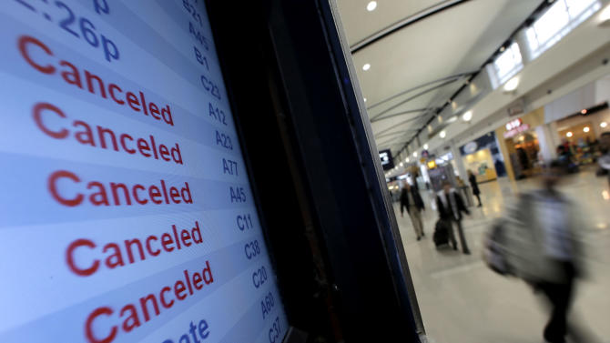 FILE - In this Monday, Oct. 29, 2012, file photo, travelers on Delta Airlines pass a departure screen Monday, Oct. 29, 2012, in Detroit. Delta said Superstorm Sandy hurt fourth-quarter profits by $100 million. That, plus special charges, left Delta Air Lines Inc. with a profit of just $7 million. (AP Photo/Charlie Riedel, File)