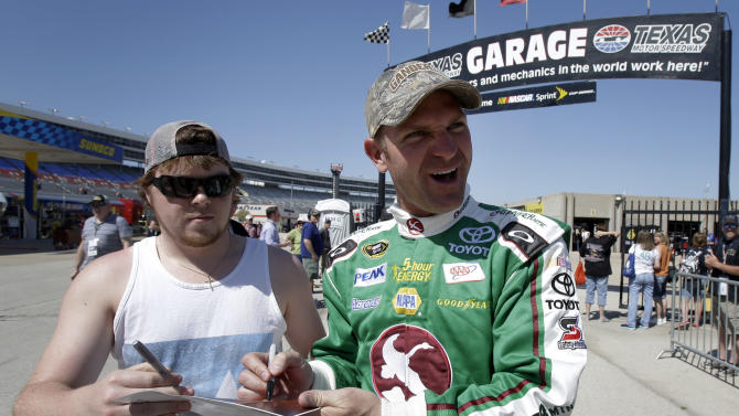 Clint Bowyer, right, signs an autograph for a fan as he walks out of the garage area during practice for the NASCAR Sprint Cup series NRA 500 auto race at Texas Motor Speedway, Friday April 12, 2013, in Fort Worth, Texas. (AP Photo/Tim Sharp)