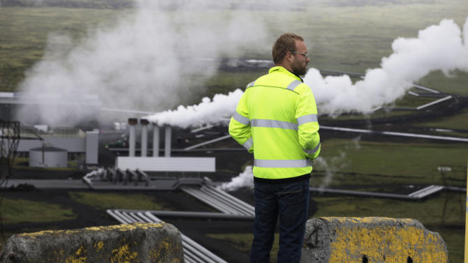 In this July 28, 2011 photo, Bergur Sigfusson, the CarbFix experiment's technical manager, surveys Reykjavik Energy's Hellisheidi geothermal power plant in Iceland. CarbFix's scientists will separate carbon dioxide from the volcanic field's steam and pump it underground to react with porous basalt rock, forming limestone, to see how well the gas most responsible for global warming can be locked away in harmless form. (AP Photo/Brennan Linsley)