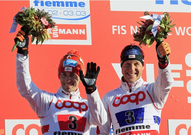 Silver medallists Wilhelm Denifl and Bernhard Gruber of Austria celebrate on the podium at the end of the Nordic Combined Team Sprint 2x7.5km competition at the Nordic Ski World Championships in Teser